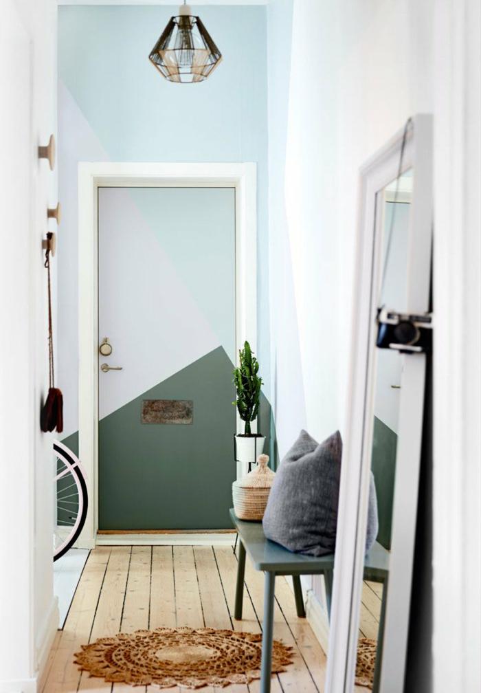 muebles de entrada, recibidor en el pasillo, suelo de tarima con tapete redondo, espejo apoyado en el suelo, paredes en azul y verde