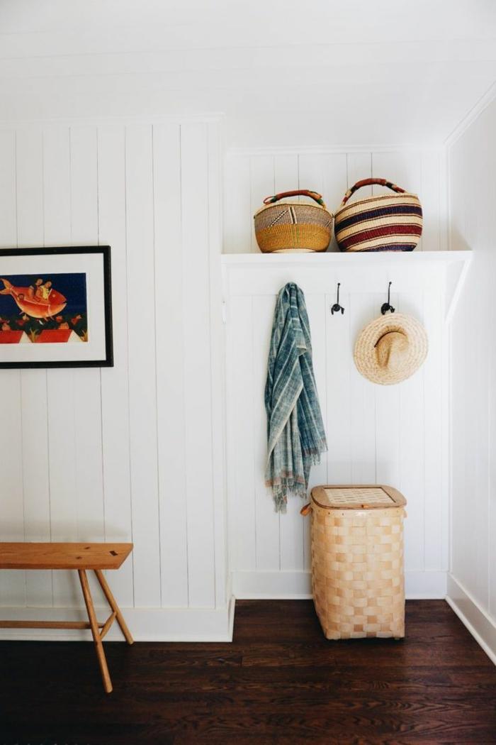 muebles de entrada, recibidor minimalista, paredes de amdera blanca, banco pequeño de amdera, canastas y ganchos