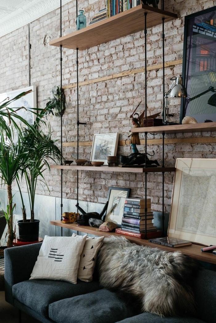 paredes decoradas, salón en estilo industrial con estantes colgantes de madera, pared de ladrillo y sofá con cojines