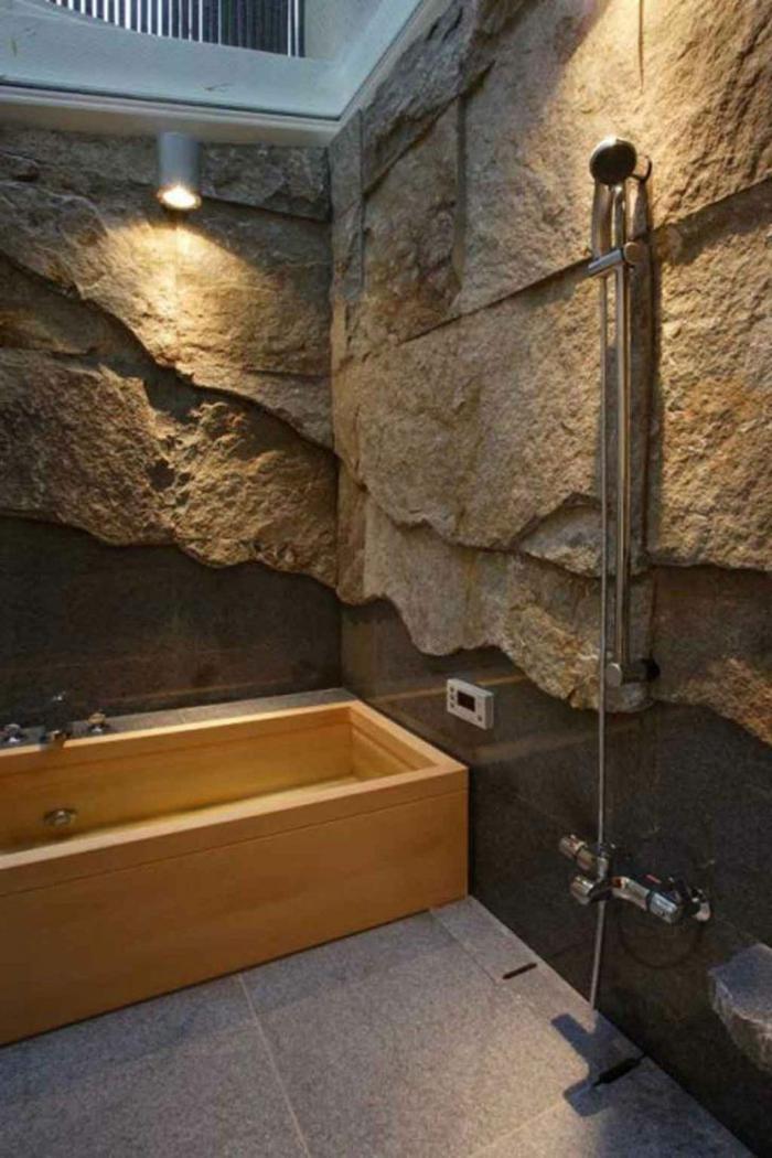 paredes decoradas, baño con bañera de madera y ducha de mano, pared de piedra decorativa, luz artificial