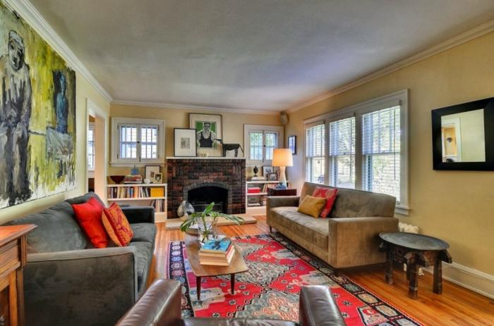 salon, salon grande en colores terrosos, sofás en gris y beige, decoración en la pared, chimenea de leña