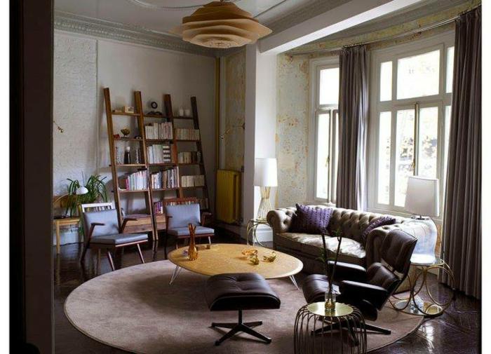 habitacion vintage, sala de estar con estantería de escaleras de madera, alfombra oval y sofá en color ocre