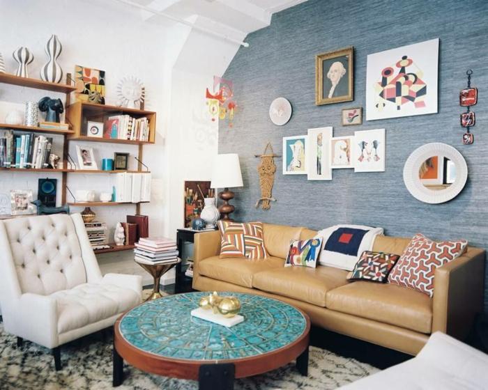 habitacion vintage, paredes con mucha decoracion original, muebles vintage, sillón en capitoné, y sofá en beige