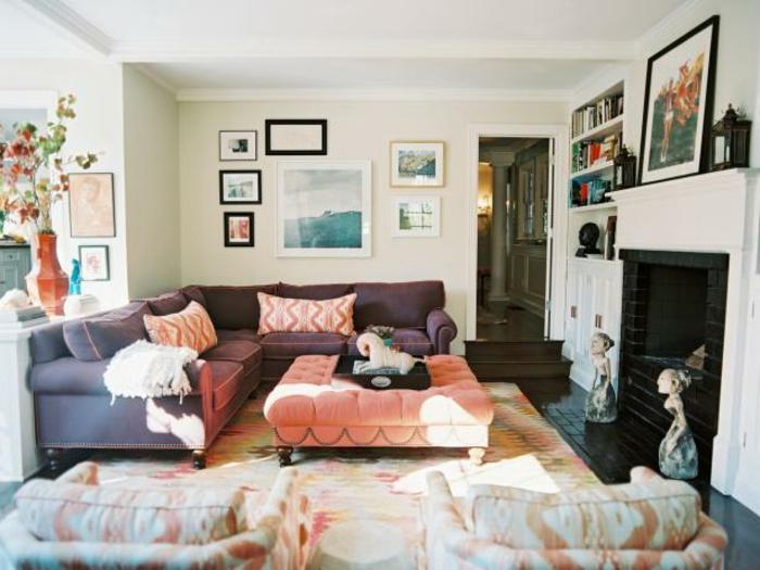 habitacion vintage, mesa baja tapizada en capitoné, sofá grande en color lila, mucha decoracion en las paredes