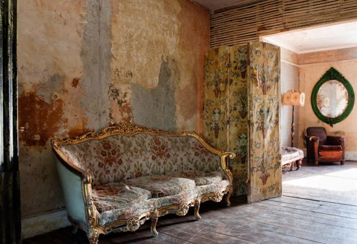 vintage, salón vintage, paredes con efecto muy desgastado, grande sofá con bordes dorados tapizada con estampado de motivos florales