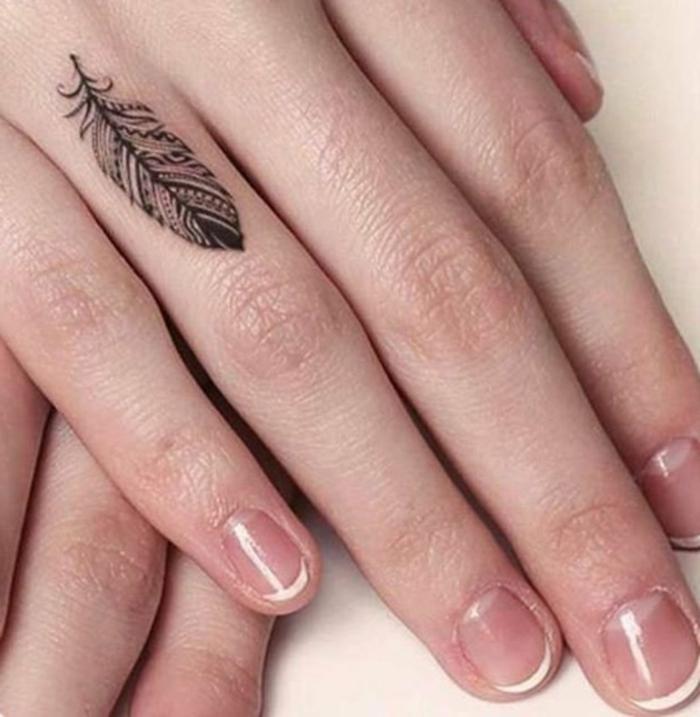 tatuajes en la muñeca, mano de mujer con manicura, tatuaje minimalista en el dedo anular, pluma negra