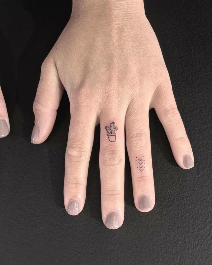 tatuajes en la muñeca, mano de mujer, idea de tatuaje con cactús en el dedo medio y flechas en el anular