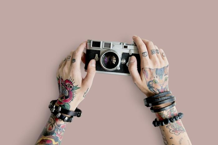tatuajes en la muñeca, manos colgando una camara de fotos, muchos tatuajes en la mano y el antebrazo, tatuajes pequeños de camara, corazon y el simbolo de paz en los dedos