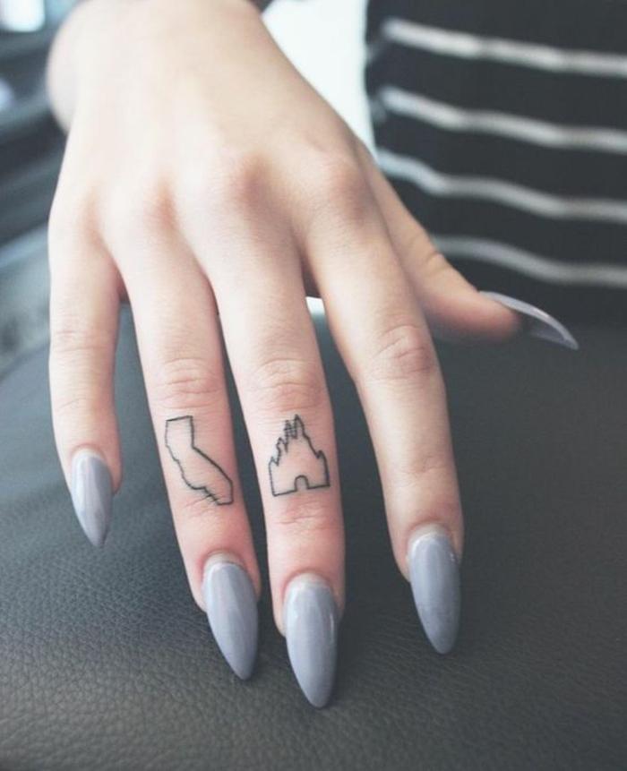 tatuajes en la mano, mano de mujer con manicura gris, dedo medio y dedo anular con tatuajes del castillo de Disney y el mapa de California