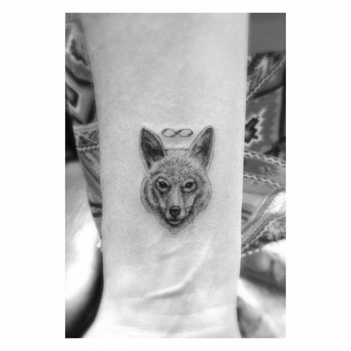 tatuaje lobo, tatuaje minimalista feminino en la muñeca, cabeza de lobo con el signo de eternidad, foto en blanco y negro
