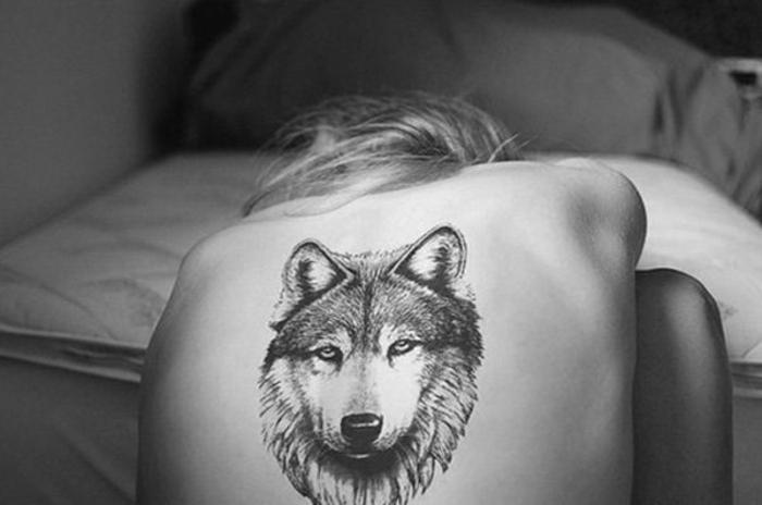 tatuajes de lobos, mujer con pelo largo, tatuaje en la espalda, cabeza de lobo en estilo realista. foto en blanco y negro