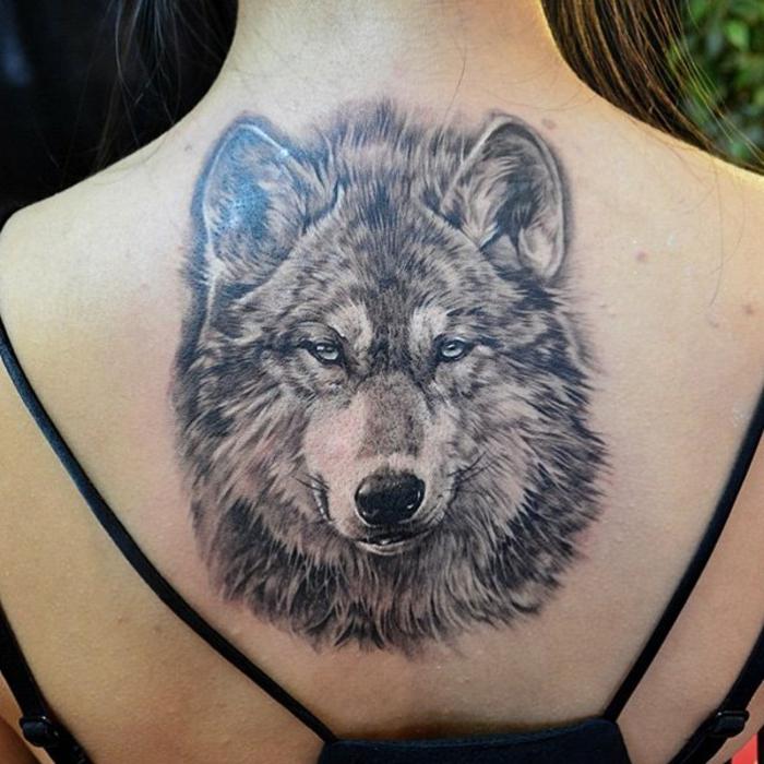 mejores tatuajes, tatuaje realista, espalda de mujer con blusa negra, cabeza de lobo grande con ojos azules