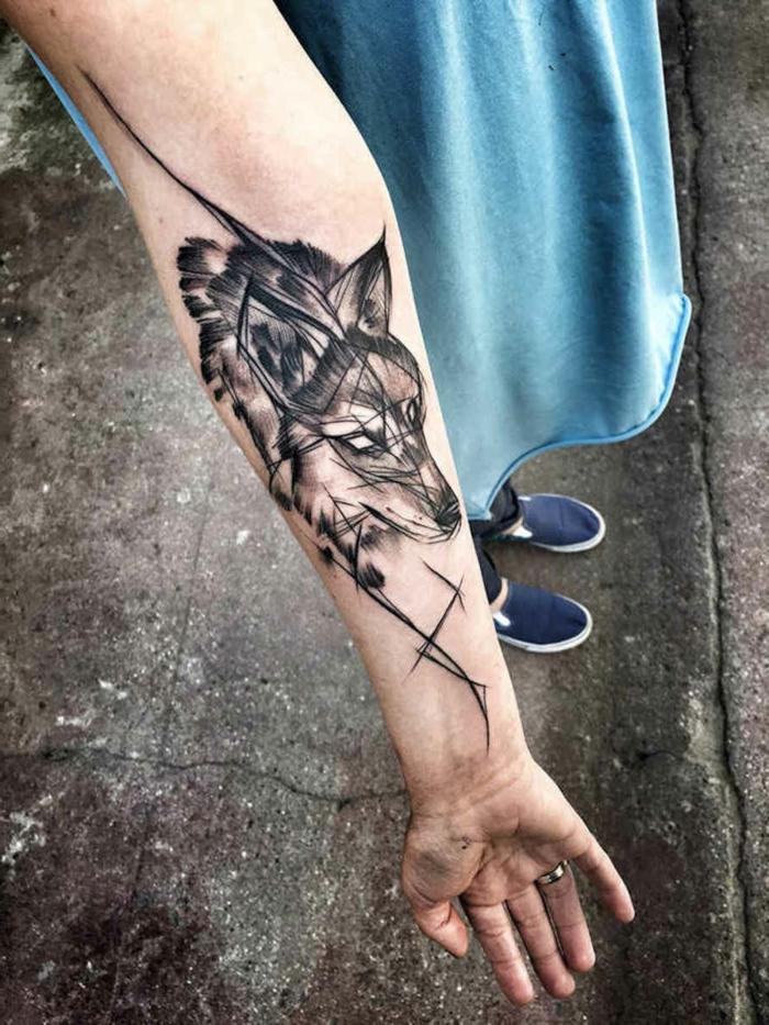 tatuajes de animales, mujer con vestido azul,tatuaje femenino en el antebrazo, cabeza de lobo en estilo geométrico