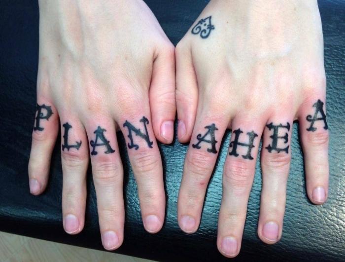 tatuajes en la mano, manos recién tatuados con tatuaje de letras en los dedos, cara de ratón en la mano