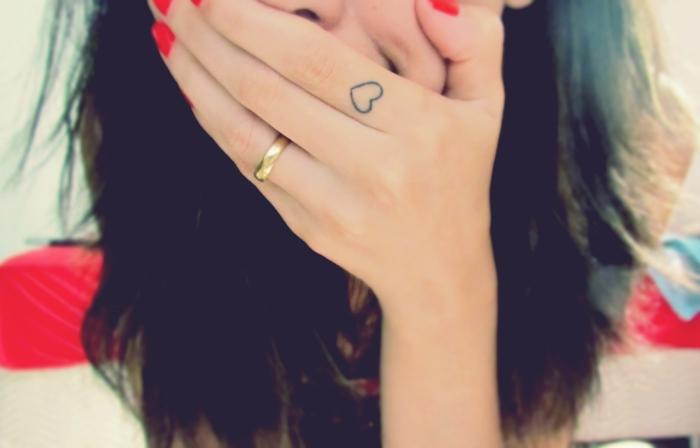 tatuajes en la mano, mujer con uñas rojas, pelo largo y anillo de boda, tatuaje de corazón pequeño en el índice