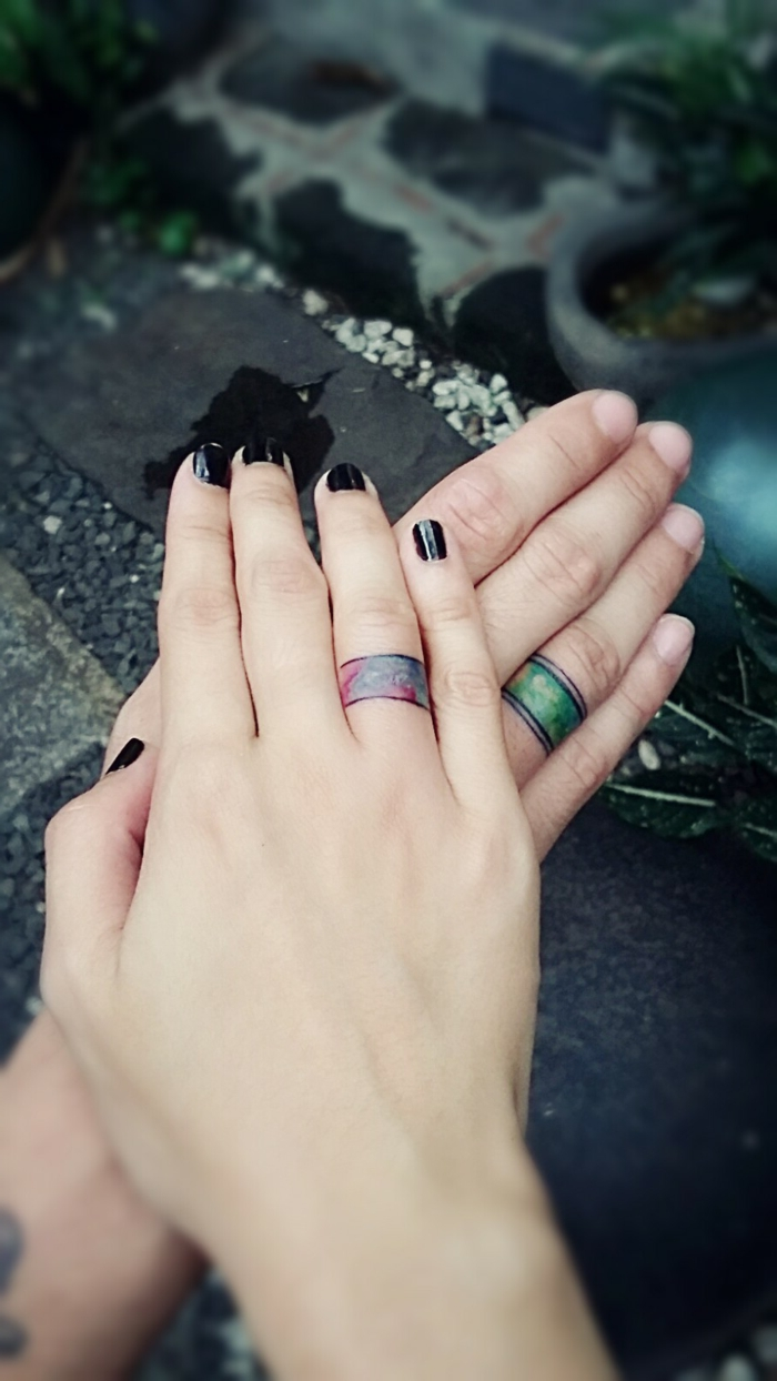tatuajes en la mano, idea de tatuajes para parejas con anillos tatuados en el dedo anular, anillo en púrpura para ella y anillo en verde para él