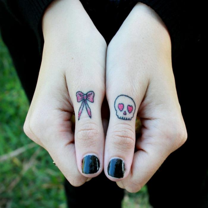 tatuajes mujer, mano de mujer con esmalte negro, pulgares tatuados con lazo y calavera con ojos corazones