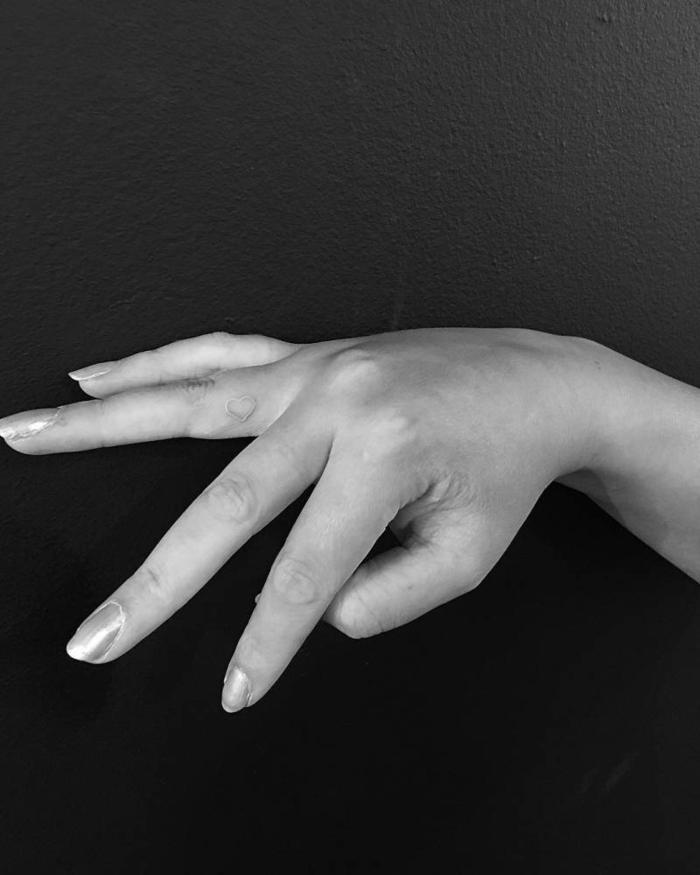tatuajes dedo, mano de mujer, foto en blanco y negro, tatuaje con corazon de color dorado en el dedo anular
