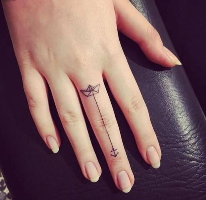 tatuajes dedo, mano de mujer, tatuaje minimalista con barca de papel y flecha negra en el dedo corazón