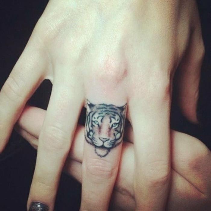 tatuajes dedos, tatuaje en con cabeza de tigre en el dedo medio, mano de mujer con manicura y piel blanca