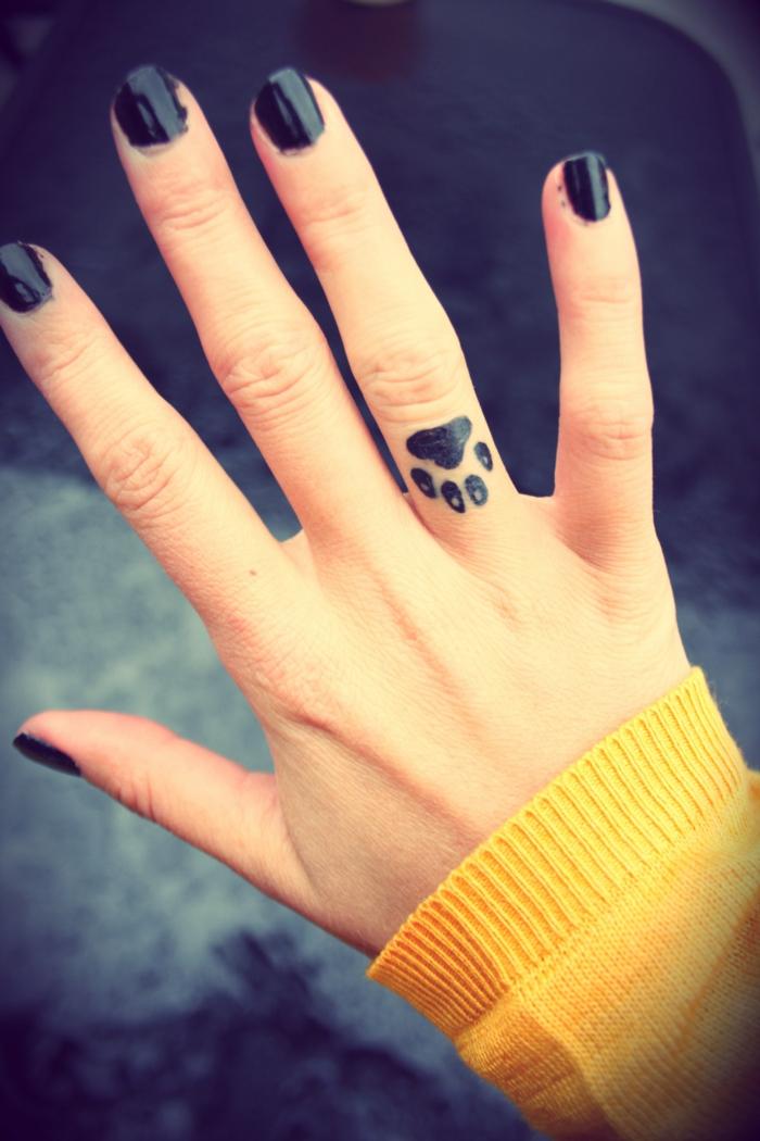 tatuaje corazon, mano de mujer con manga larga, esmalte negro en las uñas, tatuaje con pata de perro en el dedo anular