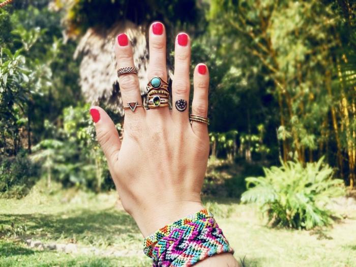 tatuajes mujer, mano de mujer con uñas rojas, muchos anillos y pulseras, tatuaje con luna y sol en el anular