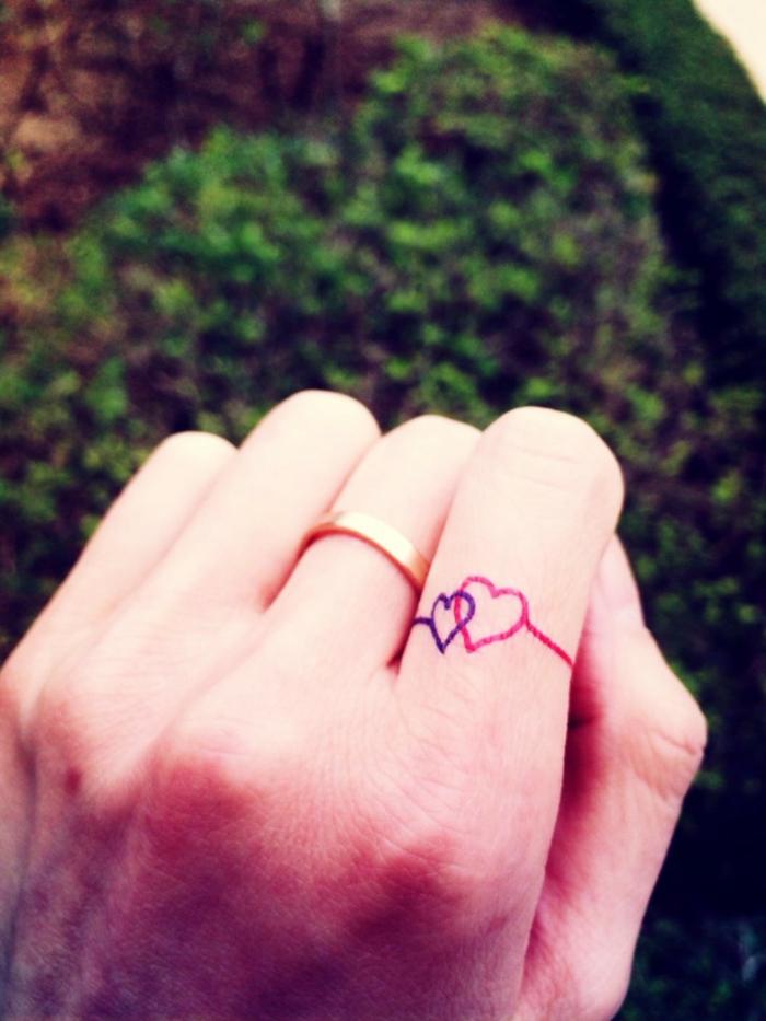 tatuajes mujer, idea de tatuaje romántico con corazones cruzados en púrpura y rosado, anillo de plata en el dedo medio