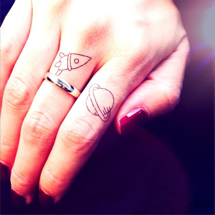 tatuajes mujer, tatuajes pequeños de saturno y una nave espacial, mano de mujer con uñas rojas, anillo en el dedo corazón