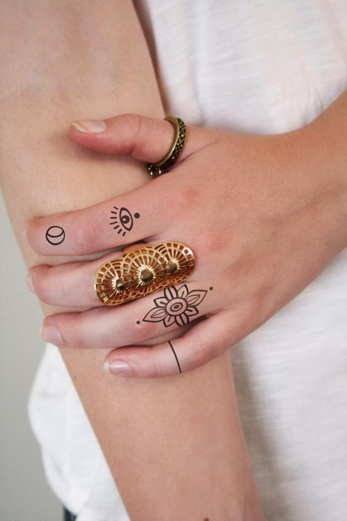 tatuajes mujer, mano de mujer con anillos en dorado, ojo de la providencia, luna y flor en el índice y el anular