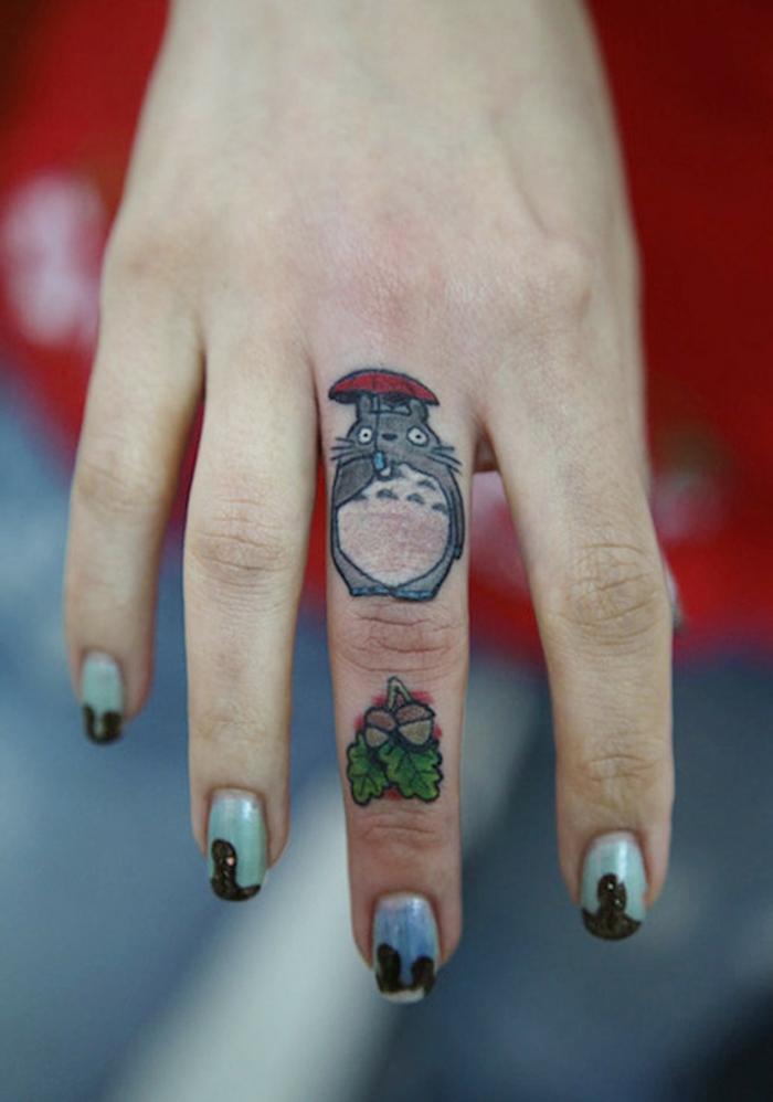 tatuajes mujer, mano de mujer con manicura, dedo medio tatuado con gato con paraguas y avellanas de color