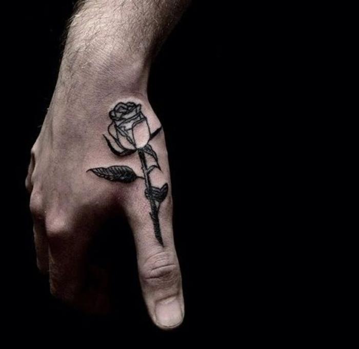 ideas para tatuajes, tatuaje grande en la muñeca y el pulgar, rosa con hojas en negro, mano de hombre