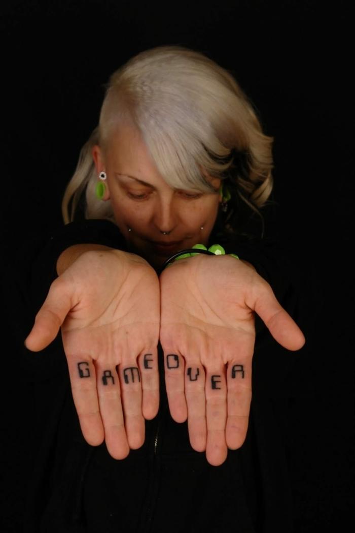 tatuajes en los dedos, mujer con pelo rubio y piercing, tatuaje de frase en la cara posterior de los dedos, game over