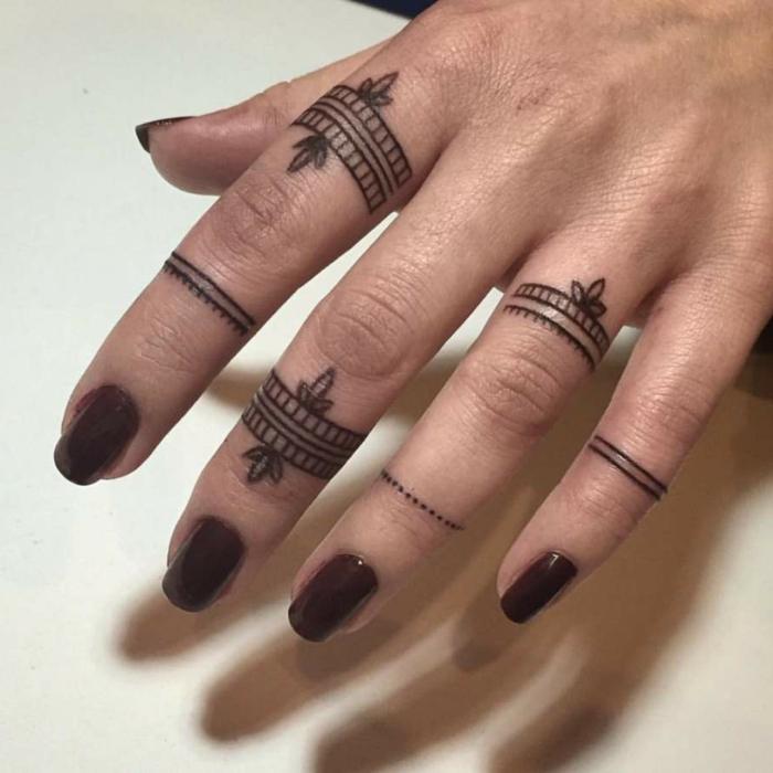 tatuajes en los dedos, mujer con uñas en carmín, dedos con tatuajes negros de anillo diferente tipo
