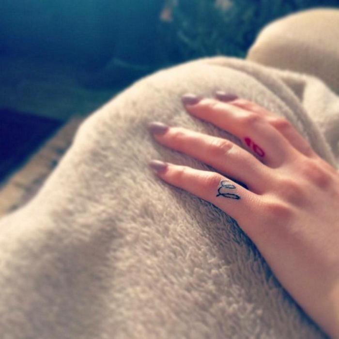 tatuajes en los dedos, mano de mujer con manicura, tatuajes minimalistas en negro y rojo en el menique y el dedo medio