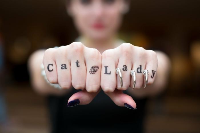 tatuajes en los dedos, idea de tatuaje para mujer con frase y diamante en los dedos, anillos como uñas de gato