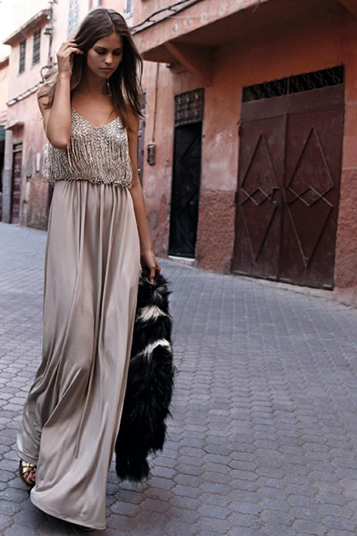 vestidos para ir de boda, vestido largo beige de satén con toque juvenil, pelo suelto ondulado, chaqueta peluda negra