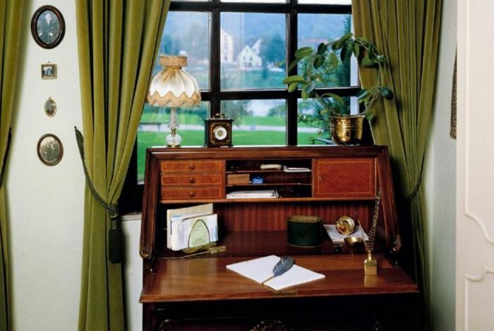 habitacion vintage, escritorio de madera viejo, cortinas en verde de terciopelo, objetos vintage