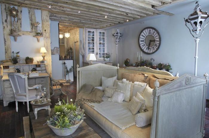 salones vintage, interior en azul claro con vigas de madera y mueble s con efecto envejecido, cama con cabecero vintage