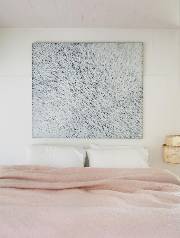 cuadros para dormitorios, pinturas grandes encima de la cama, ambiente en tonos pastel, paredes en blanco y cobijas en rosado