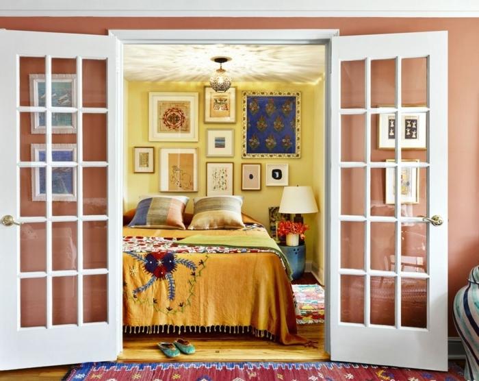 interior en estilo vintage, dormitorio acogedor con puerta original de madera, paredes en amarillo y salmón, cuadros para dormitorios matrimonio