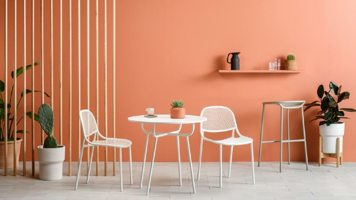 terraza de colores, ejemplo de decoración de terrazas con encanto, separador de ambientes de pelos de madera, pequeña mesa con sillas, paredes pintadas en color melocotón