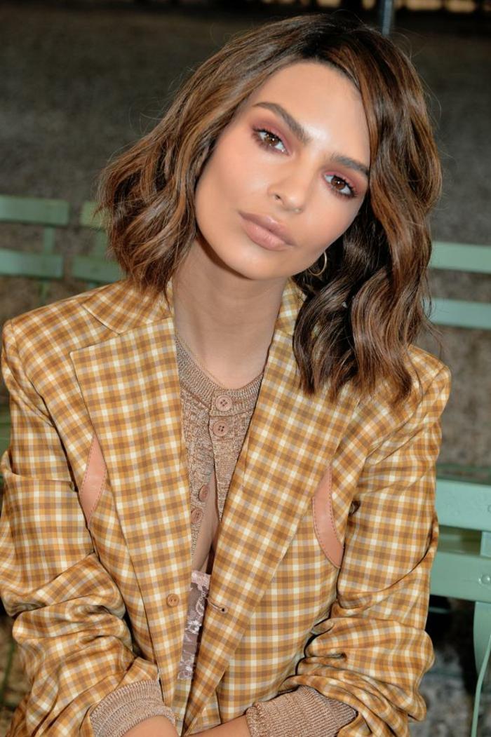 cortes de pelo modernos, media melena ondulada, cabello con mechas mas claras, color chocolate, chaqueta en estampado de cuadrados color ocre