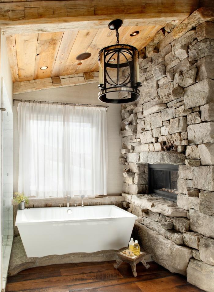 ejemplo acogedor de baño rústico con bañera moderna, baños rusticos abuhardillados, pared de piedra natural con chimenea empotrada