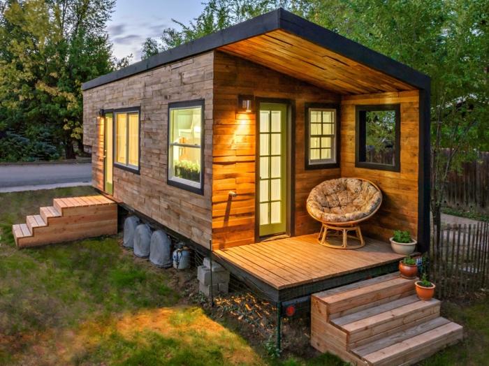 minicasas, micro vivienda prefabricada con muchas ventanas, cubierta pequeña con sillón cómodo, estrellas de madera