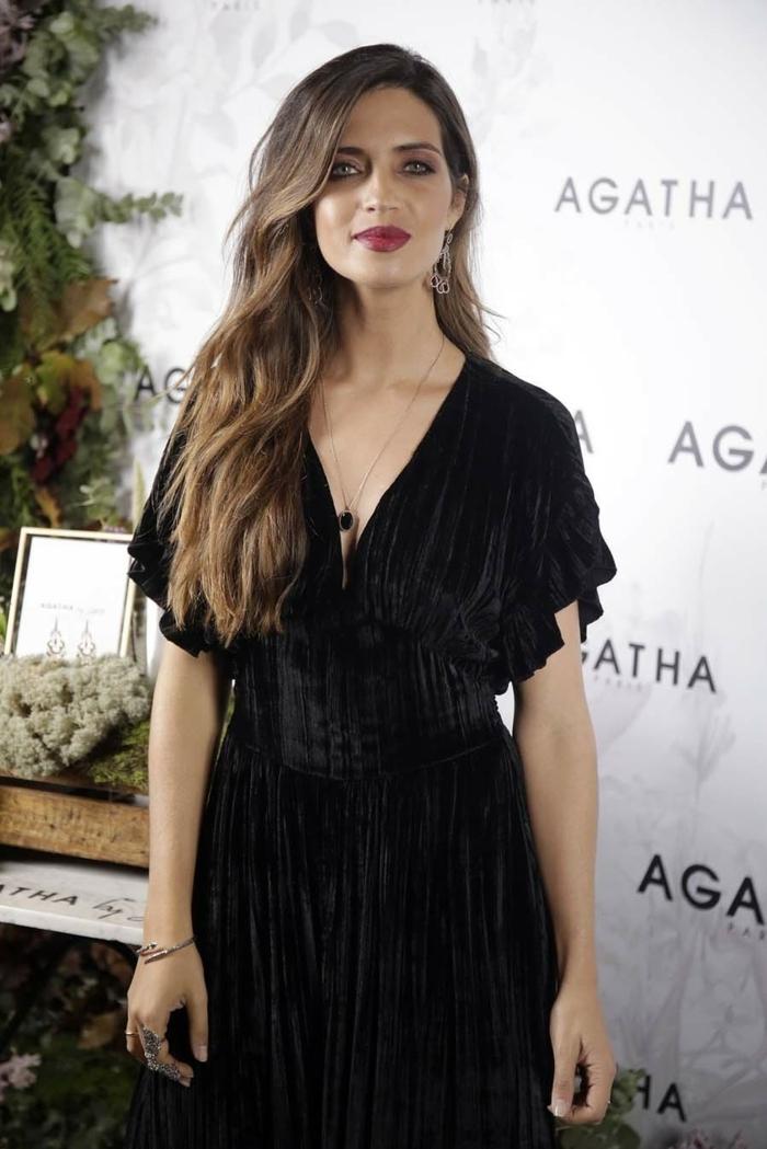 cortes de pelo largo, larga melena castaña peinada a un lado con mechas rubias, pelo muy largo y grueso, vestido elegante en negro