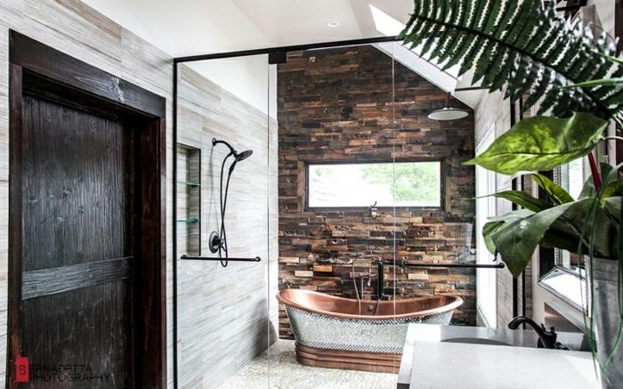 propuesta moderna de un baño con decoración con elementos rústicos, bañera en marrón u plata, pared de piedra y decoración de plantas verdes