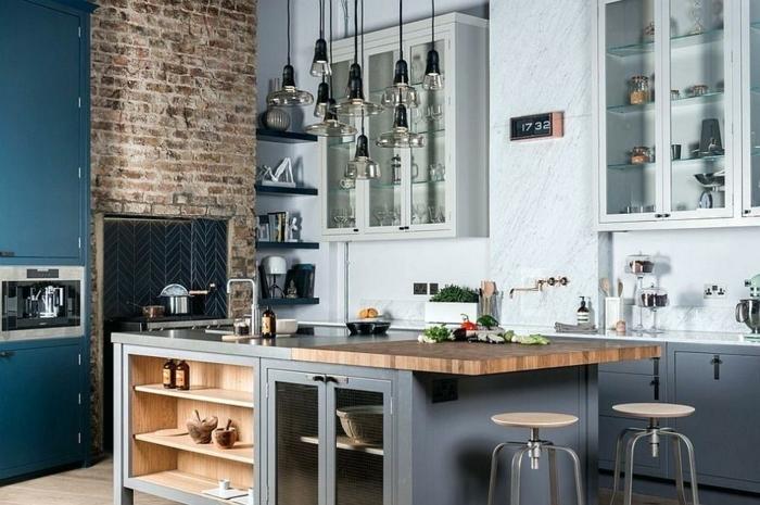 cocina moderna con detalles en azul, muebles de cocina de madera pintadas en azul y gris, pared de ladrillos