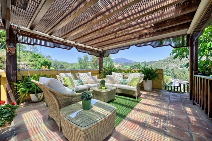 luminosa y espaciosa terraza con grande pergola, muebles de rattan en color claro, detalles en verde y muchas macetas con plantas