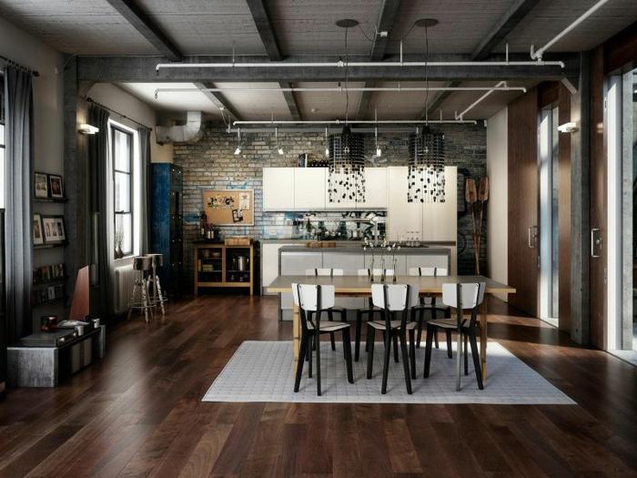 salón espacioso en estilo industrial con techo con vigas de madera, muebles de cocina de madera pintados en beige, pared de ladrillos y suelo de parquet