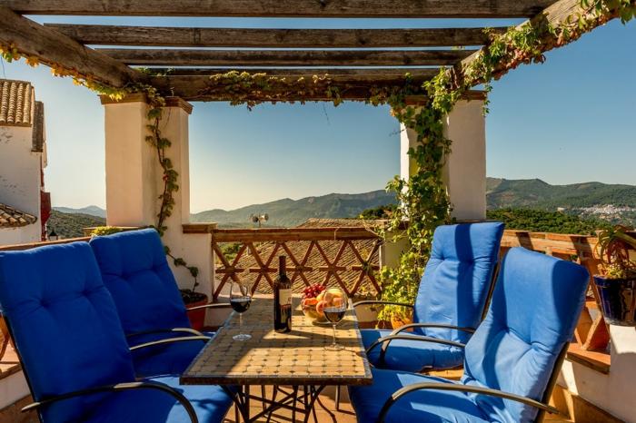diseño coqueto y toque romántico, terraza con sillones tapizados en azul saturado, pergola de madera, muchas plantas verdes